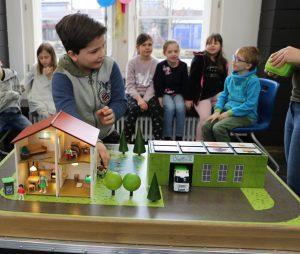 Kind steht vor Elekrospiel Von wegen faule Gurke