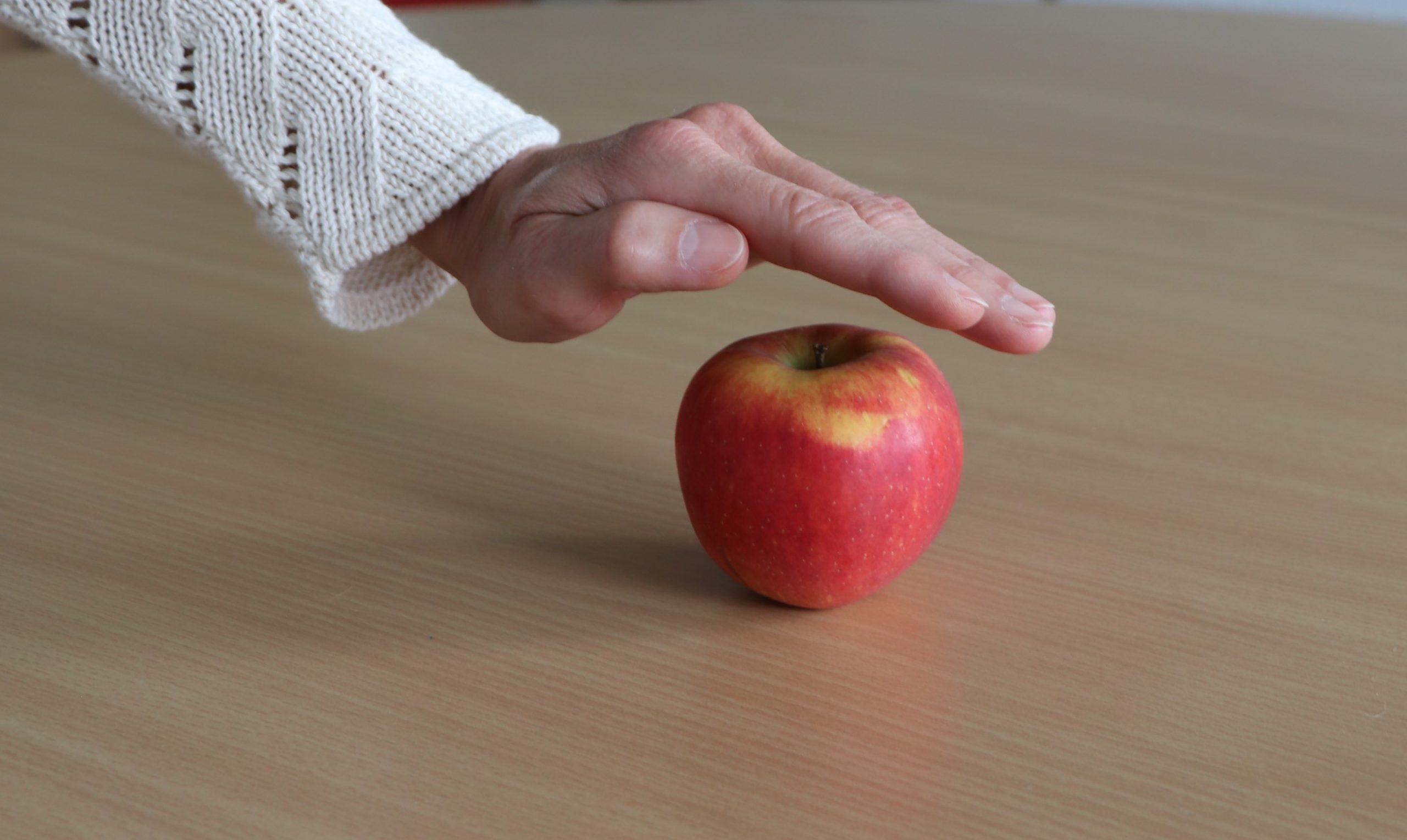 Hand wird schützend über Apfel gehalten