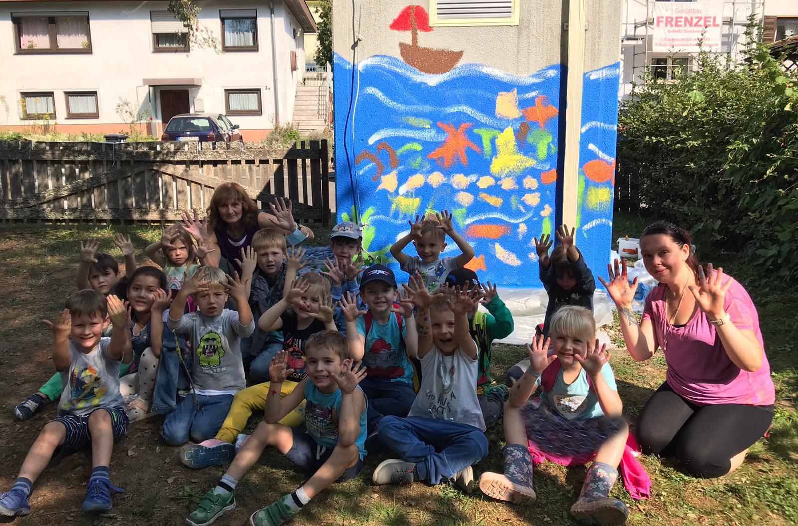 Kinder sitzen vor bemalter Pumpstation