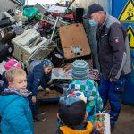 Kinder stehen vor geöffnetem Container mit Elektroschrott