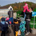 Kinder stehen vor Papiercontainer