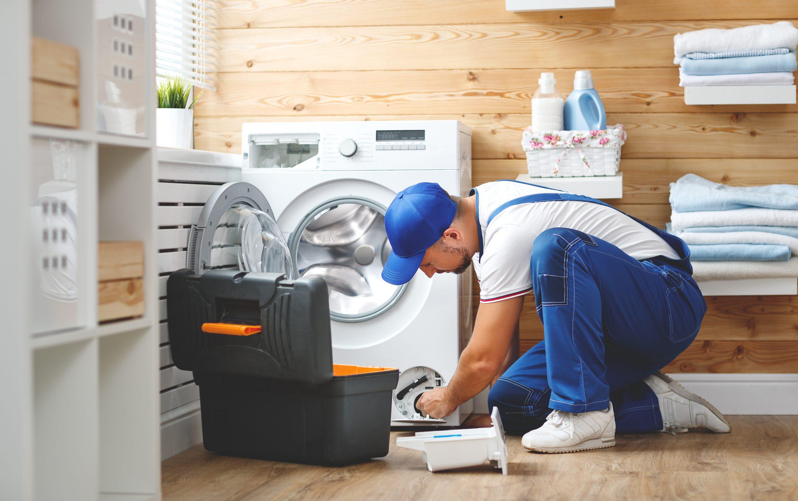 Mann repariert Waschmaschine