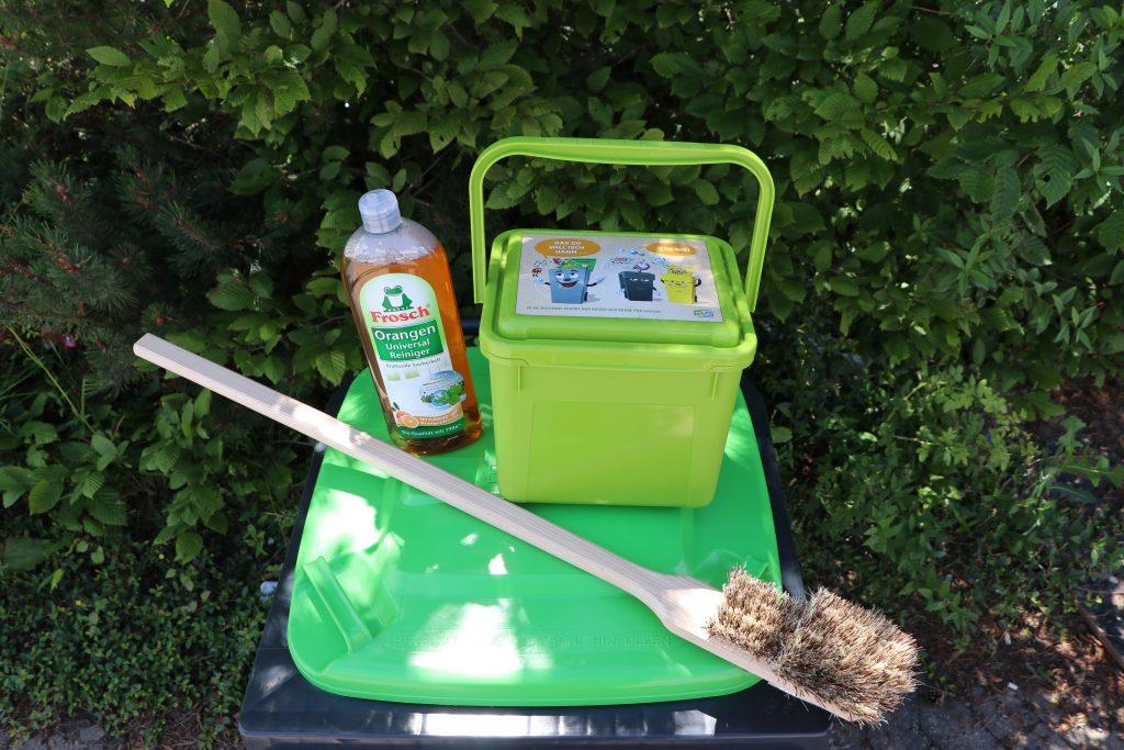 auf einer Abfalltonne mit grünem Deckel liegen eine Bürste eine Flasche Reiniger und ein Gefäß zum Sammeln von Biogut