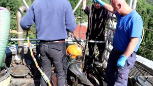 Berufstaucher wird per Seilwinde von Kollegen in den Faulturm herabgelassen